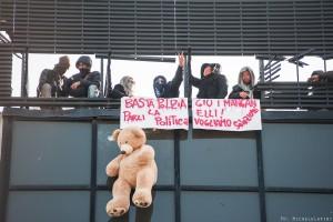 Bologna, 20 ottobre 2015: dalle finestre dell'Ex-Telecom spuntano cartelli e quella che diventerà la mascotte del corteo del 24 ottobre.