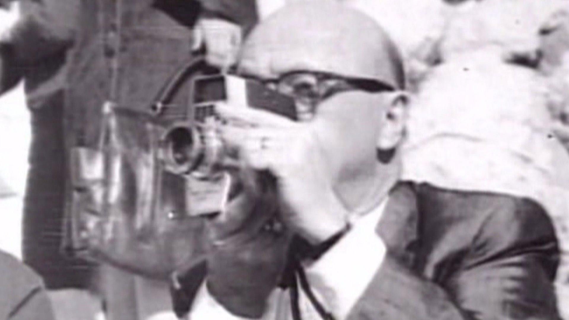 Abraham Zapruder mentre filma l'assassinio di J.F. Kennedy